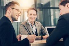 Жизнерадостный мужской говорить с счастливыми коллегами Стоковое фото RF