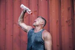 Жизнерадостный мужчина поднимает бутылку воды Он льет вне aqua на его голове и закрывает его глаза с удовольствием Он усмехается стоковые фотографии rf