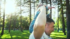 Жизнерадостный отец держа его ребенка на плечах и закручивая вокруг outdoors сток-видео