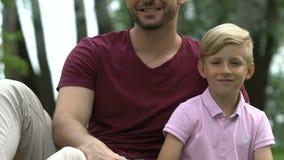 Жизнерадостный отец и сын показывая большие пальцы руки вверх, удовлетворенный с обслуживаниями курорта акции видеоматериалы