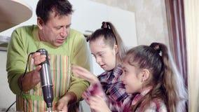 Жизнерадостный отец семьи с дочерьми имеет потеху подготавливая обедающий использующ смеситель кухни сток-видео