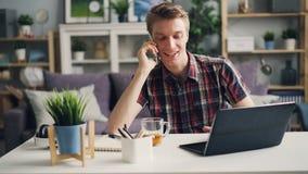Жизнерадостный парень говорит на мобильном телефоне и использует деятельность ноутбука дома делая далекую работу самомоднейшая те акции видеоматериалы