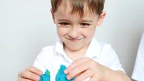 Жизнерадостный, радостный мальчик играя с модельной смесью для работы акции видеоматериалы