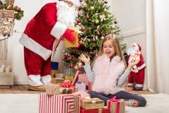 Жизнерадостный ребенк получая подарки от добросердечного Санты Стоковые Фотографии RF