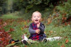 Жизнерадостный ребенк сидит на пути в лесе Стоковые Фотографии RF