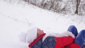 Жизнерадостный ребенок в красных скольжениях куртки через снег в санях от высокого холма и смеха счастливая девушка играя рождест акции видеоматериалы