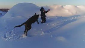 Жизнерадостный ребенок играя с собакой в снеге видеоматериал