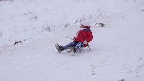 Жизнерадостный ребенок сползает вниз холм в снеге в санях и смехе Снег летает к девушке в стороне Праздники рождества в парке сток-видео