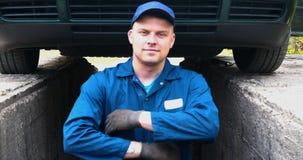 Жизнерадостный ремонтник автомобиля на ремонтах улицы двигатель и нижняя часть автомобиля акции видеоматериалы