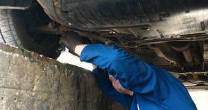 Жизнерадостный ремонтник автомобиля на ремонтах улицы двигатель и нижняя часть автомобиля сток-видео