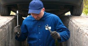 Жизнерадостный ремонтник автомобиля на ремонтах улицы двигатель и нижняя часть автомобиля видеоматериал