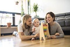 Жизнерадостный родитель играя с его ребенком на поле на живя комнате стоковые фото