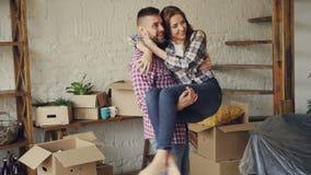 Жизнерадостный сильный парень завихряет его подругу и целует ее пока двигающ к новому дому после покупать его романтично сток-видео