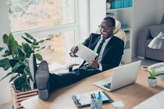 Жизнерадостный, смеющся над, смешной, положительный финансист положил ноги на таблицу, стоковое фото