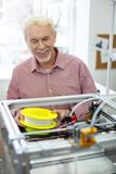 Жизнерадостный старший человек усмехаясь пока заменяющ нить стоковое фото rf