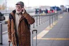 Жизнерадостный старый джентльмен в стеклах наслаждается связью телефона стоковая фотография