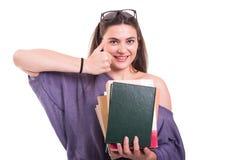 Жизнерадостный студент делая как знак и держа книги Стоковая Фотография