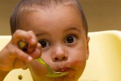 Жизнерадостный счастливый ребенок младенца ест с ложкой стоковая фотография