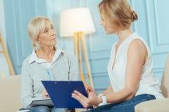 Жизнерадостный умный финансовый советник усмехаясь пока помогающ постаретой женщине Стоковая Фотография RF