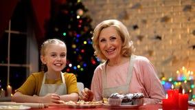 Жизнерадостный усмехаться бабушки и девушки, удовлетворяемый с рождеством варя, праздники стоковые изображения rf