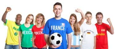 Жизнерадостный французский поклонник футбола с шариком и вентиляторы от другого countri стоковое фото