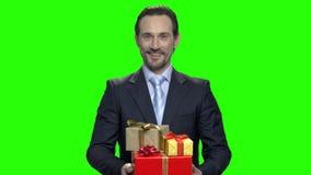 Жизнерадостный человек в деловом костюме с подарочными коробками видеоматериал