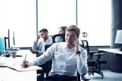 Жизнерадостный человек в офисе отвечая телефону стоковая фотография rf