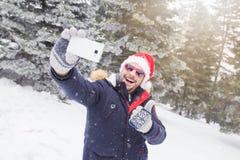 Жизнерадостный человек в шляпе и солнечных очках santa принимая selfie на снежный день стоковое изображение rf