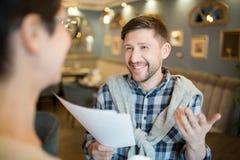 Жизнерадостный человек говоря к коллеге о бумагах Стоковые Фотографии RF