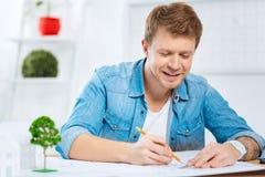 Жизнерадостный человек усмехаясь пока сидящ и рисующ линии Стоковые Фотографии RF