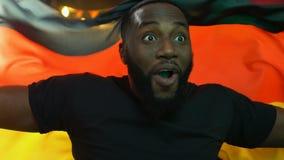 Жизнерадостный черный вентилятор развевая немецкий флаг, радуясь национальная победа спортивной команды видеоматериал