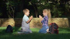 Жизнерадостный школьник и школьница играя хлопающ игра сидя в парке после учить на перерыве школы сток-видео