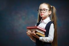 Жизнерадостный элементарный пук книги владением школьницы стоковые изображения