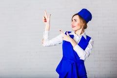 Жизнерадостный stewardess в голубой крышке делает жесты с ее руками стоковые изображения