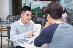 2 жизнерадостных азиатских бизнесмены обсуждая с документами Стоковые Изображения