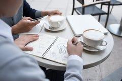 2 жизнерадостных азиатских бизнесмены обсуждая с документами Стоковое Фото
