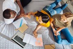 3 жизнерадостных весёлых студента начиная сделать проект Стоковые Фото
