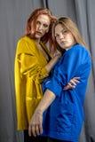 2 жизнерадостных девушки в красочных куртках танцуют и имеют потеха Стоковая Фотография RF