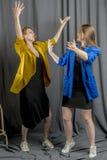 2 жизнерадостных девушки в красочных куртках танцуют и имеют потеха Стоковые Изображения
