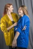 2 жизнерадостных девушки в красочных куртках танцуют и имеют потеха Стоковые Изображения RF