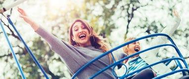 2 жизнерадостных девушки наслаждаясь их ездой на парке атракционов Стоковое Фото