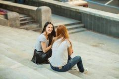2 жизнерадостных девушки сидя на лестницах Стоковая Фотография RF