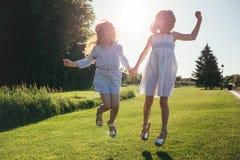 2 жизнерадостных девушки скача против захода солнца Стоковое фото RF
