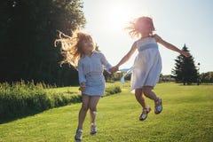 2 жизнерадостных девушки скача против захода солнца Стоковые Фотографии RF