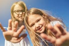 2 жизнерадостных девушки смотря камеру и протягивая их ладони Стоковая Фотография RF