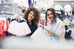 2 жизнерадостных девушки ходя по магазинам для одежд Стоковое Изображение