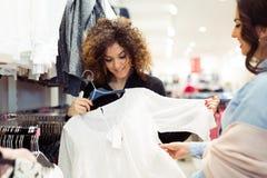 2 жизнерадостных девушки ходя по магазинам для одежд Стоковое фото RF
