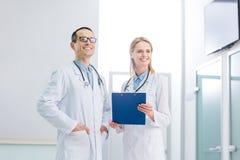 2 жизнерадостных доктора в белых пальто с стетоскопами и положением диагноза Стоковое Фото