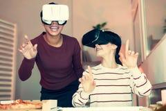 2 жизнерадостных друз имея потеху с шлемофонами VR Стоковая Фотография