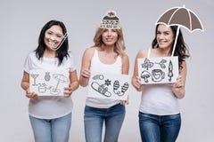 3 жизнерадостных женщины усмехаясь и мечтая о путешествовать к взморью Стоковая Фотография